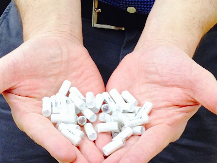 John Cutrone displays small books that have been removed from medication containers  (Photo Courtesy of Candace Kahan)